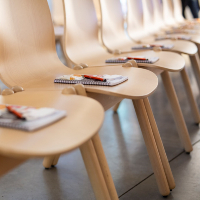 A row of empty chairs with a notepad and a pen.