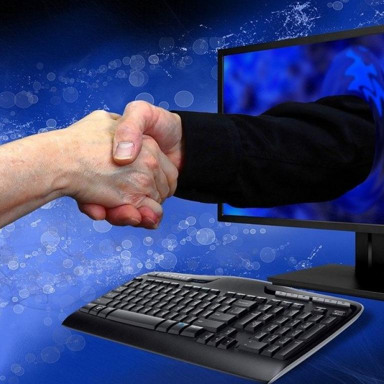 hand shake by the computer screen