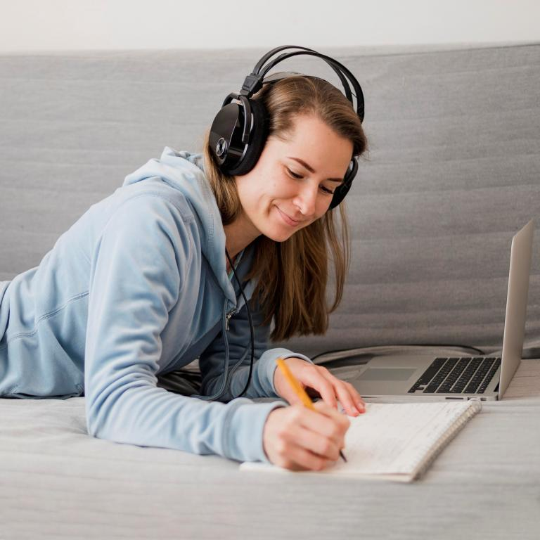 Student wearing headphones and taking notes while taking online classes on her laptop