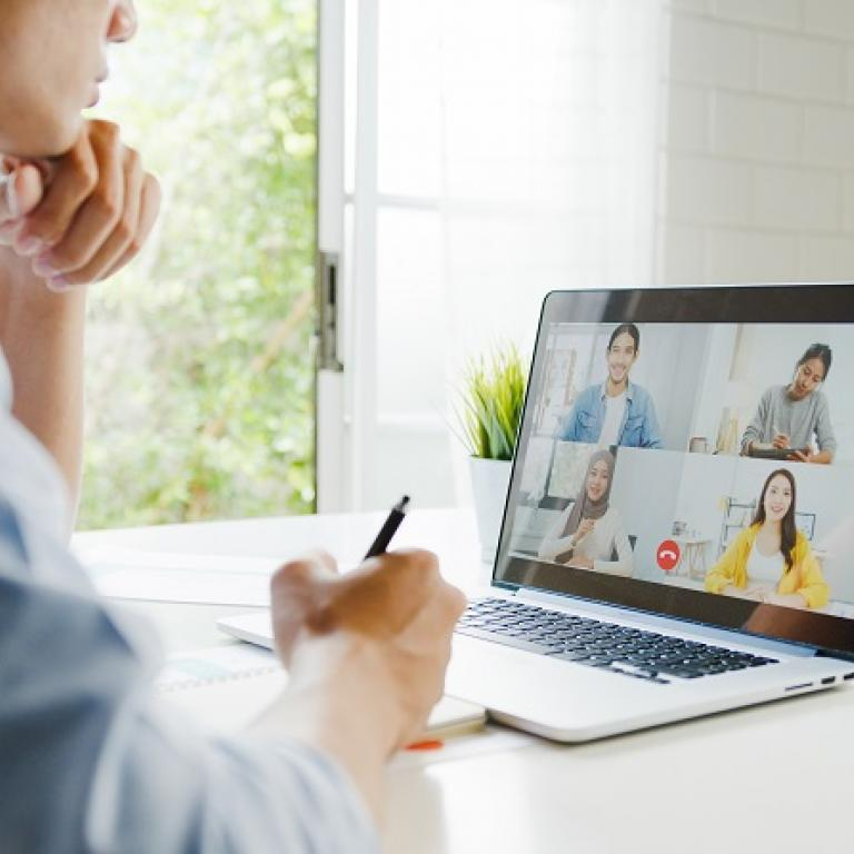 Man participating in a videoconference on his laptop
